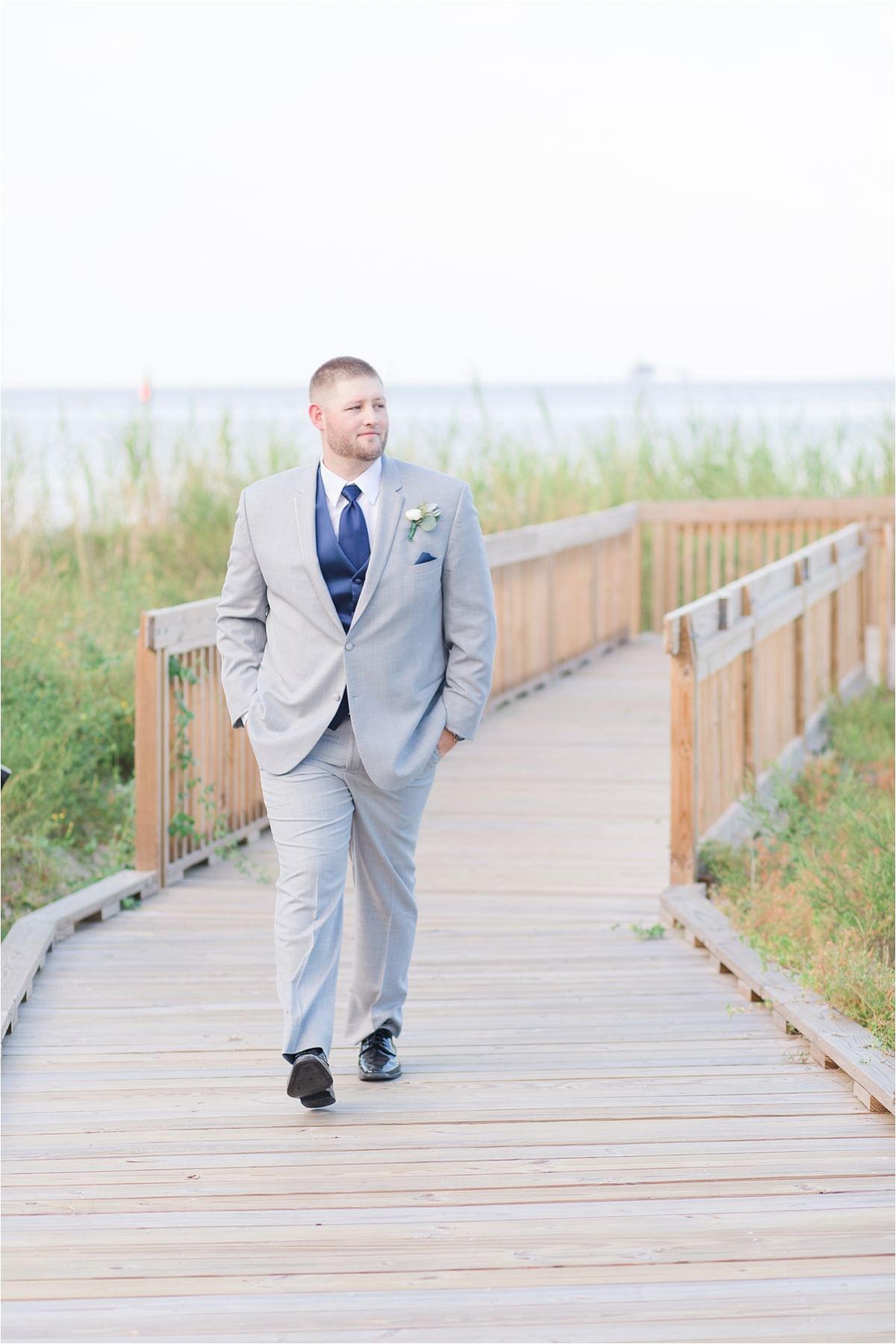 groom-navy-tie-vest-portraits-alabama-wedding-photographer-Dauphin Island Estuarium-on the beach-beach-dock