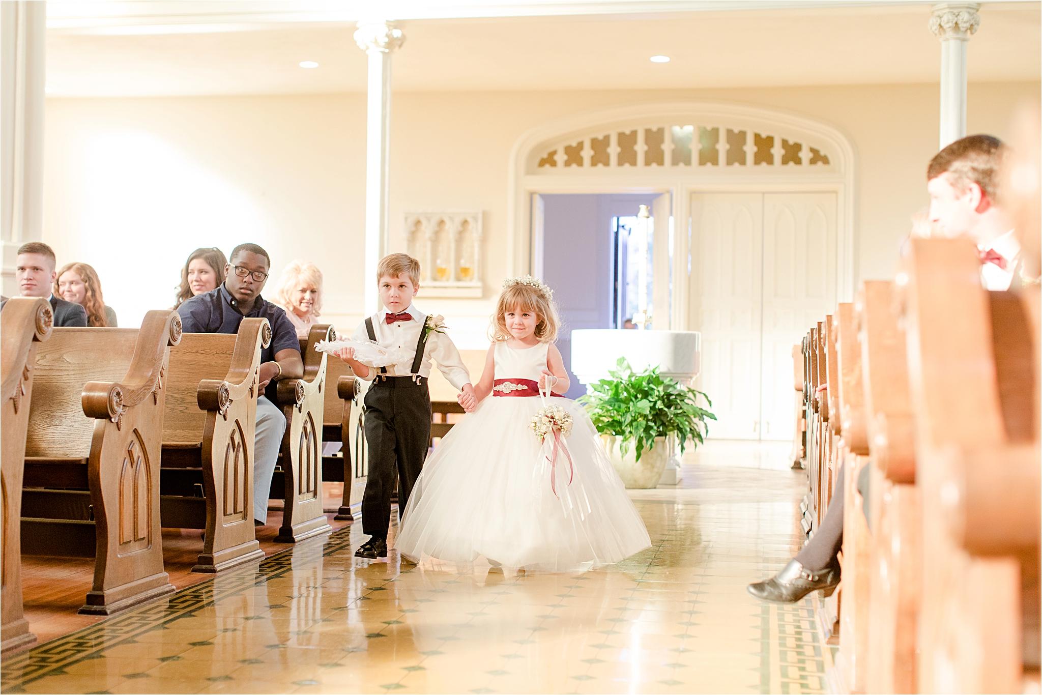 flower-girl-ring-bearer-holding-hands-walking-down-aisle-cranberry-wedding-colors-full-skirt