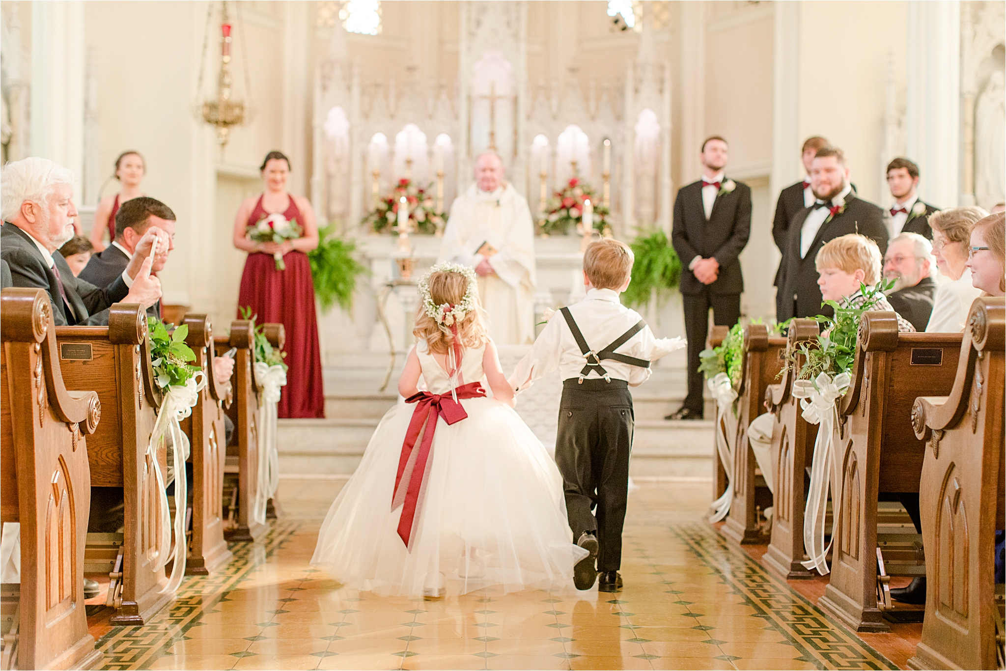 flower-girl-ring-bearer-holding-hands-walking-down-aisle-cranberry-wedding-colors-full-skirt