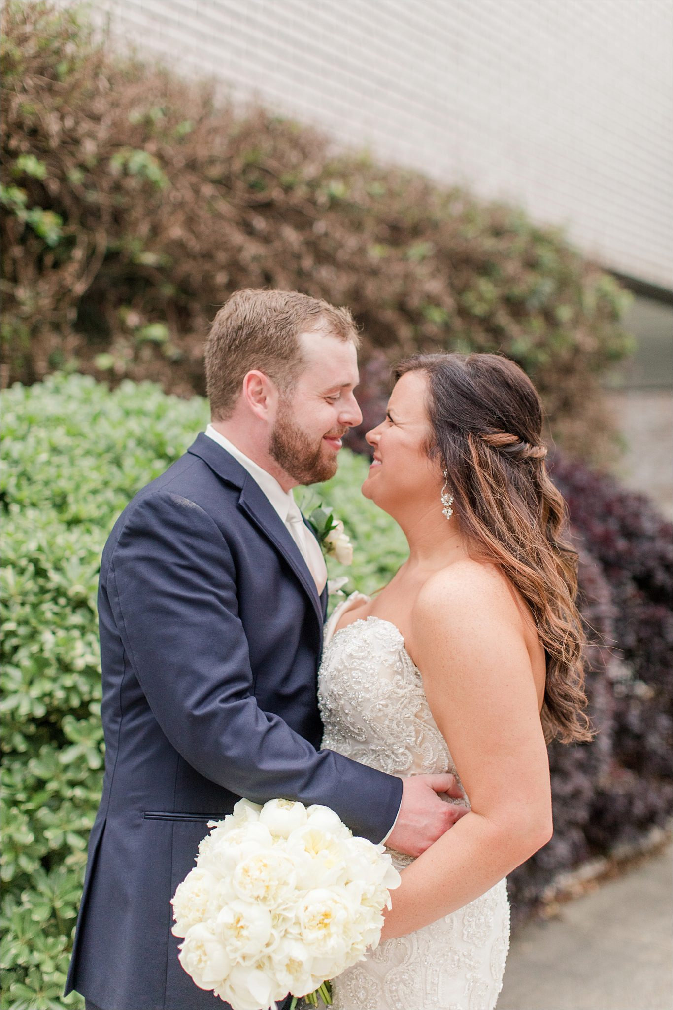 bride and groom photos-navy suit-white roses-wedding day photos-white tie-husband and wife photos