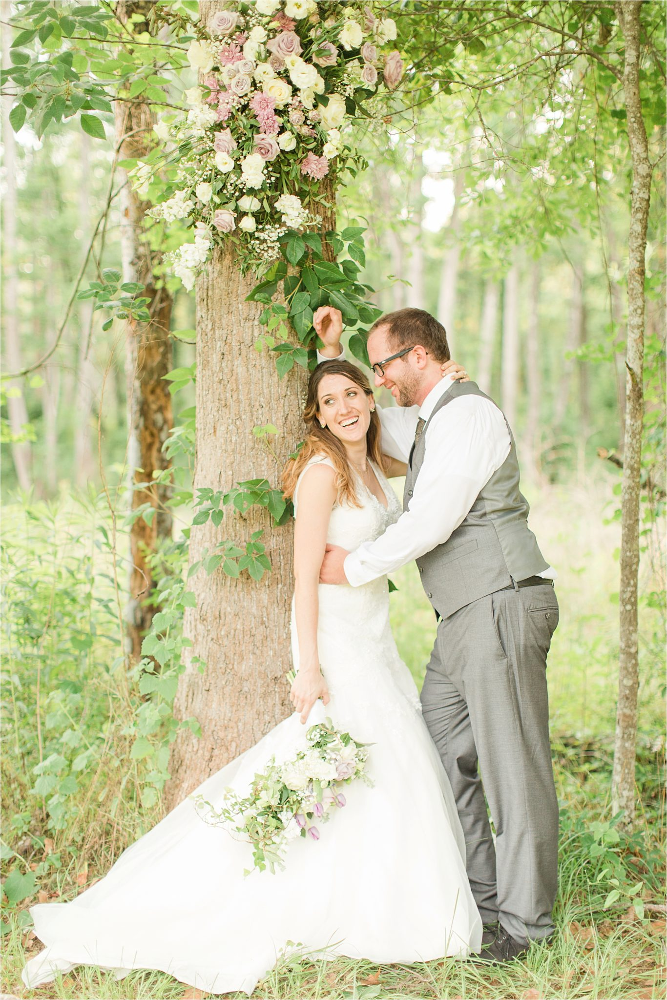backyard country wedding-decorate trees with wedding flowers-bride and groom portraits-wedding day-grey grooms suit-vest-lavender flowers-candid laughter