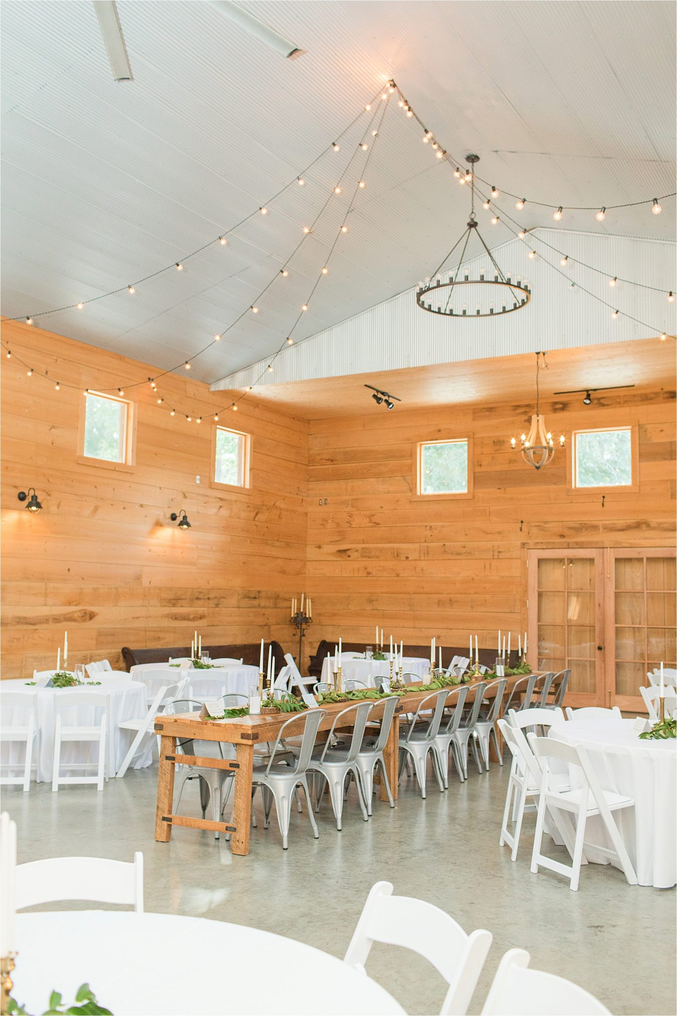 wedding-reception-alabama-venue-barn-farm-tables-metal-chairs-candle-centerpieces-hanging-lights